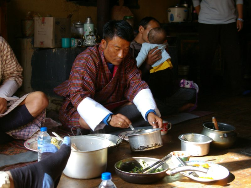 local man making food in a bhutan homestay