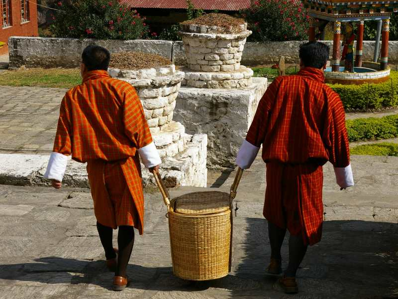 local Bhutanese people carrying water in traditional clothing