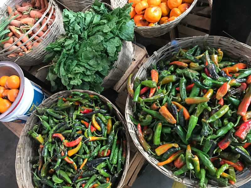 market stall with food in baskets and lots of chillies