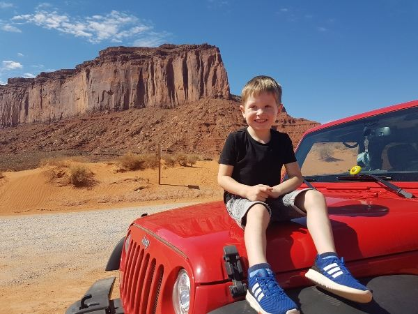 child sitting on red car with monument valley in background