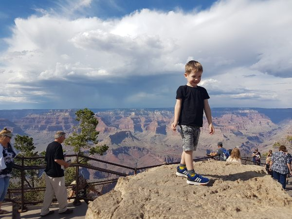 boy standing on rock with grand canyon in background