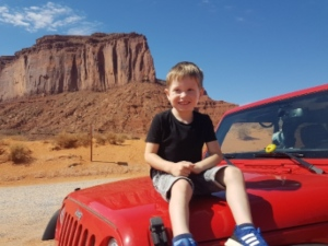 boy sitting on red car in monument valley