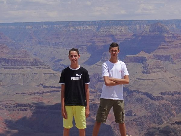 two boys standing in front of grand canyon