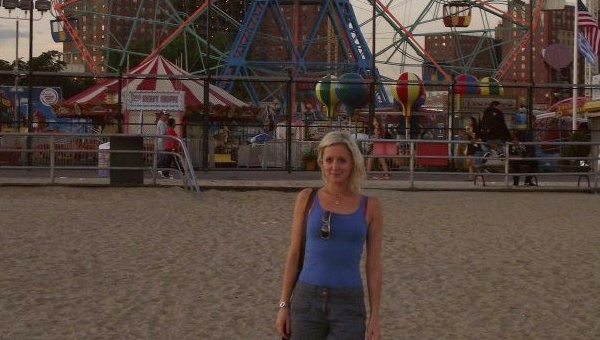 woman standing on beach with fairground behind her