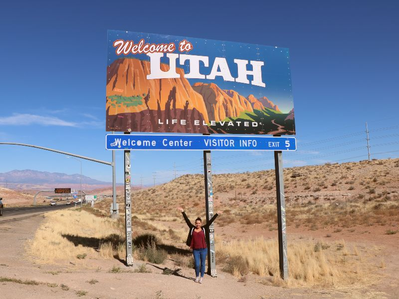 road trip sign welcome to utah with woman standing in front