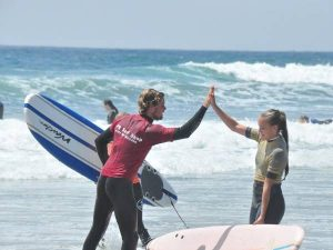teenager and surf instructor high-fiving on a beach