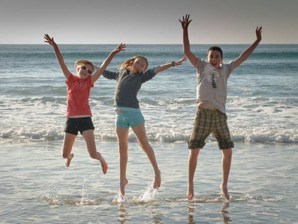 children jumping on a beach in san diego
