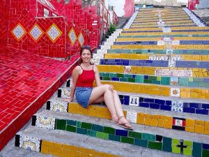 woman sat on colourful steps in mexico