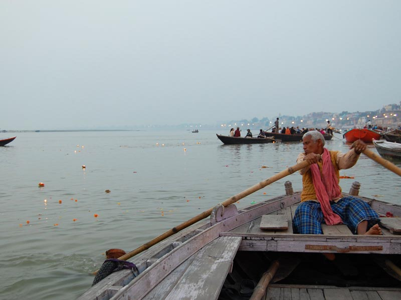 man rowing boat in varanasi