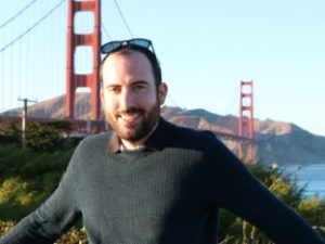 man smiling in front of golden gate bridge