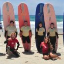 a family posing with their surf boards