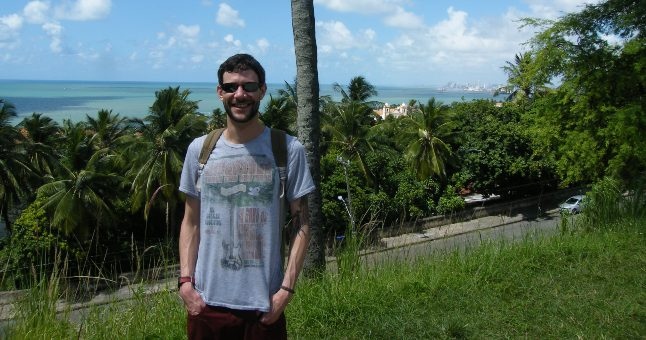man standing in front of palm trees and sea
