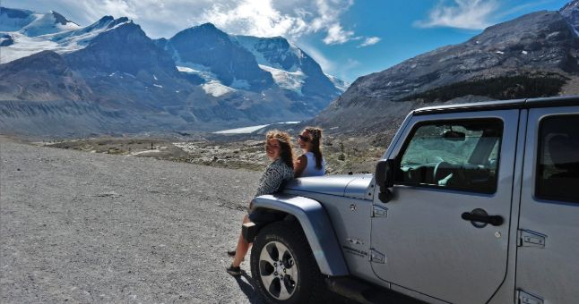 two people leaning on a car near snowy mountains