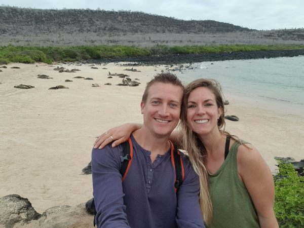 Couple in Santa Fe, Galapagos with sea lions