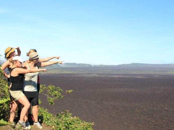 Tourists pointing across the landscape in Isabela, Galapagos