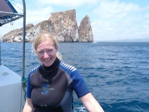 Woman on boat in front of Kicker rock in the Galapagos