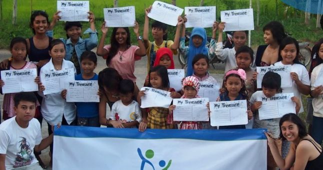 Indonesian children holding up a banner and paper