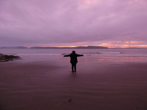 woman standing on a beach at sunset