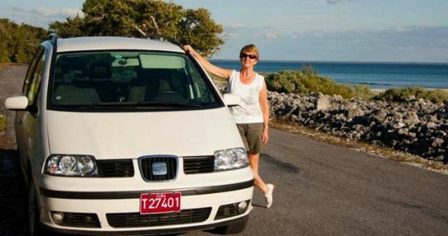 woman leaning on car with sea view