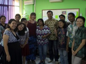 Group of Indonesian people smiling with a tourist in an office