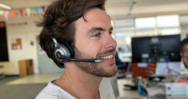 smiling man in office wearing a headset