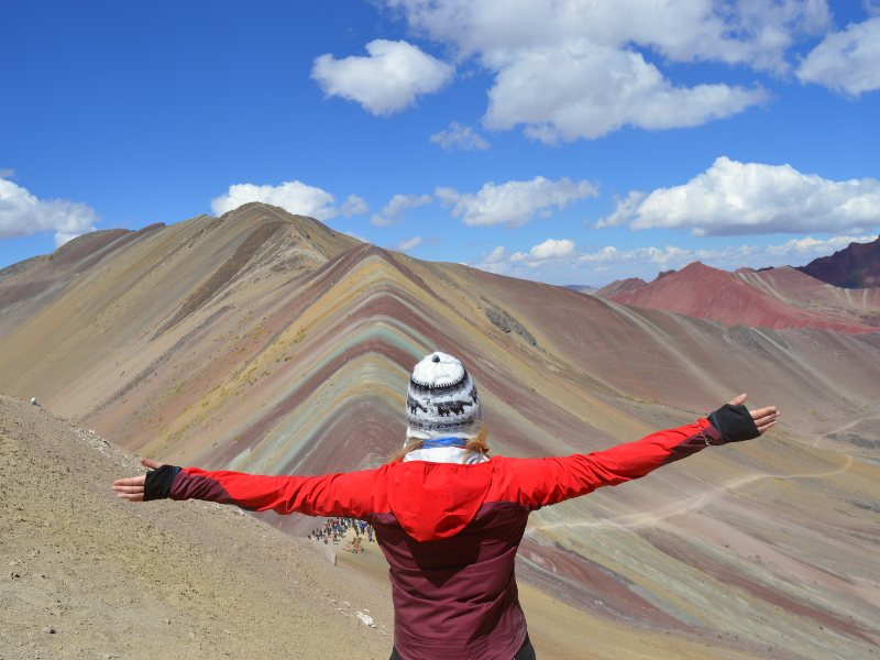 Person looking out over rainbow mountain