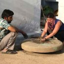 woman learning pottery from a local man in India