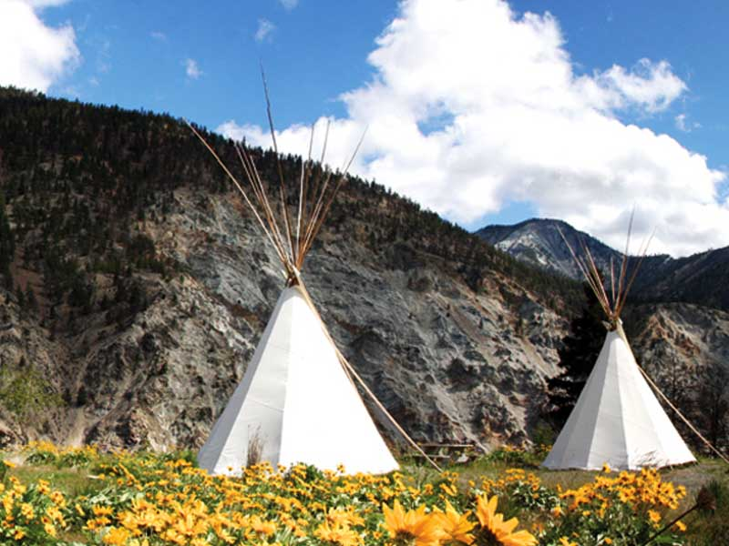 Teepees in canada with mountains in the background