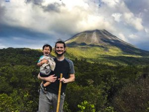 father and son standing next to volcano