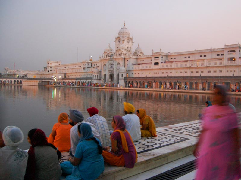 people sitting outside the temple of amritsar