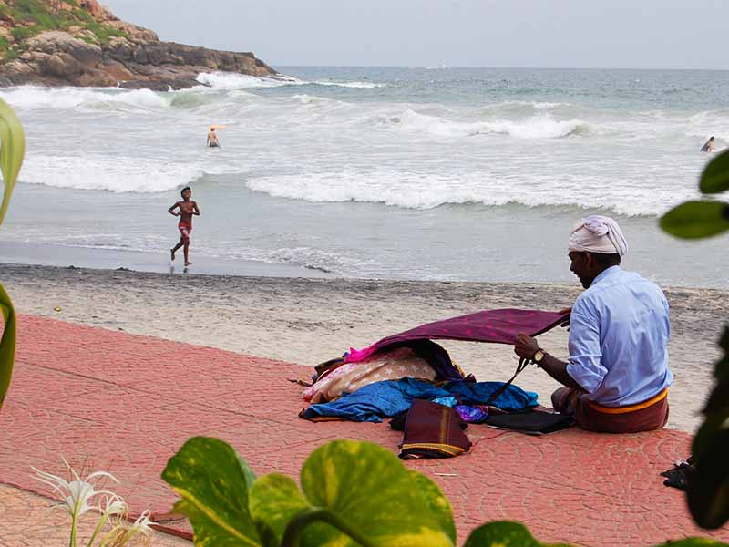 man selling things on a beach in kovalam