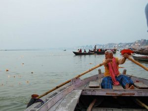 local man rowing boat on ganges river