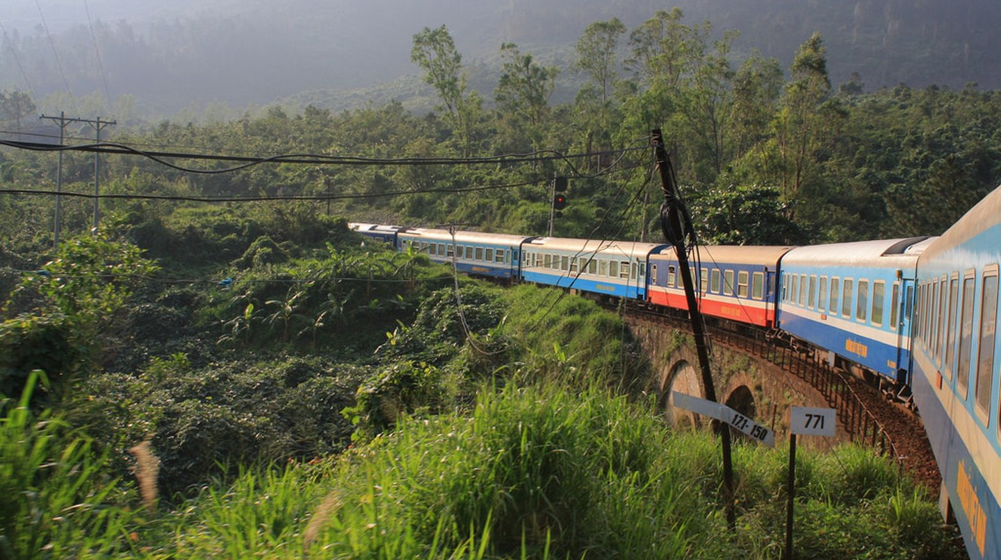 Train on bridge in Vietnam surrounded by forest.