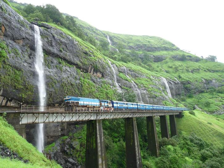 Train on bridge going by water falls.