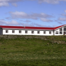 a white building with a red roof in a field