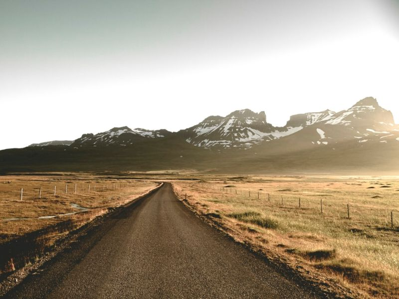 A road leading to snowy mountains
