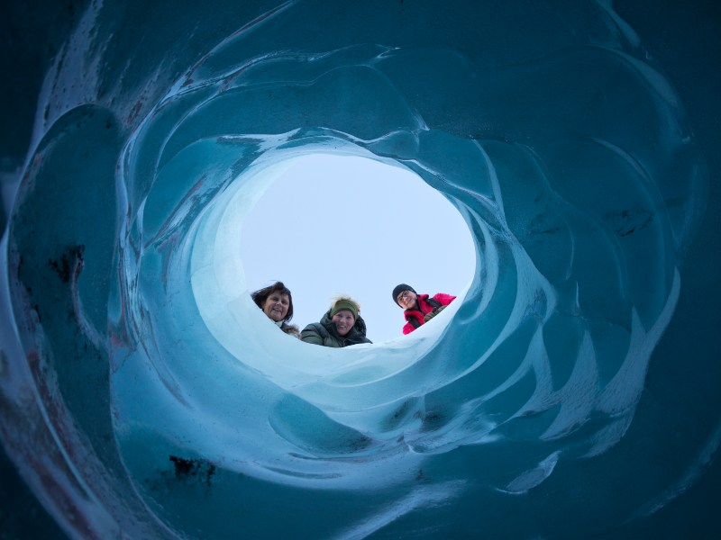 People looking through an ice hole