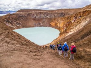Group of people walking down to volcano lake