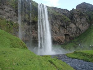 Large waterfall with green grass