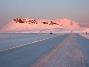 snowy road leading up to mountains with a pink sky