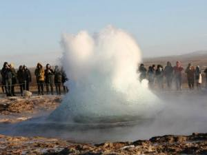 a geyser erupting with people standing and watching