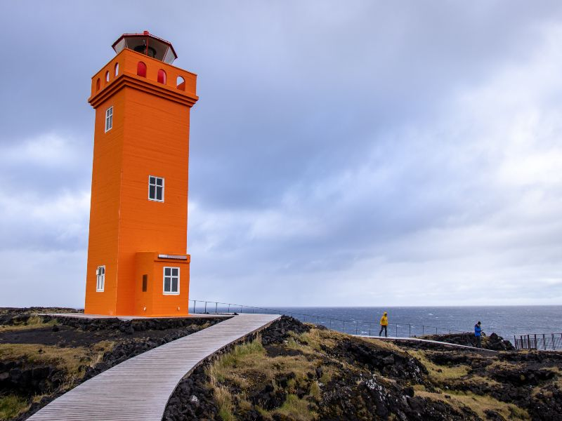 an orange lighthouse with a path leading up to it