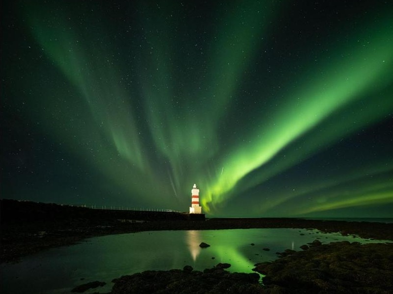 lighthouse punctuating the night sky being adorned by the northern lights