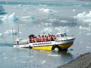 Amphibious boat driving out of an ice lake
