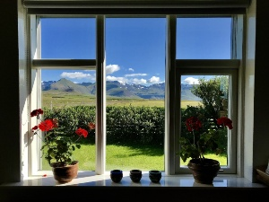 view from a windown overlooking garden and mountains