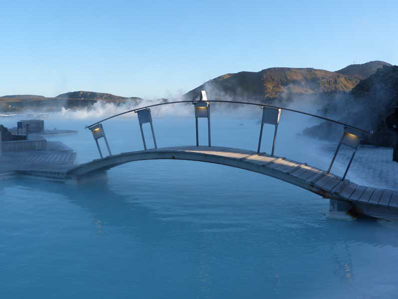 a pool with steaming water and a small bridge