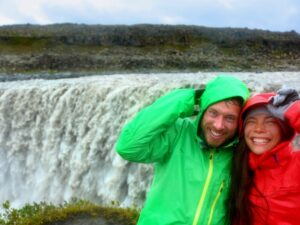 A couple standing in front of a waterfall