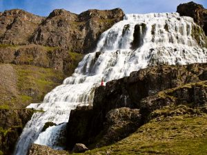 a waterfall with a person and blue skies