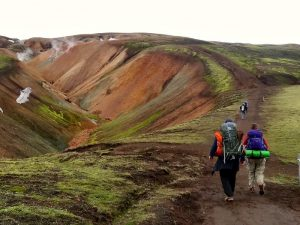 People hiking up a hill with backpacks