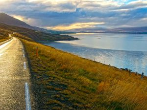 Road that runs alongside the sea with mountains